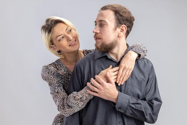 Jonge mooie paar man en vrouw gelukkig verliefd omarmen vieren valentijnsdag staande over witte muur