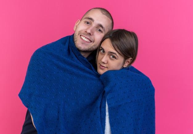 Jonge mooie paar man en vrouw gewikkeld in deken gelukkig verliefd glimlachend vrolijk staand