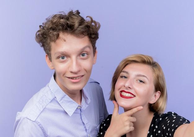 Jonge mooie paar man en vrouw glimlachend vrolijk staande over blauwe muur