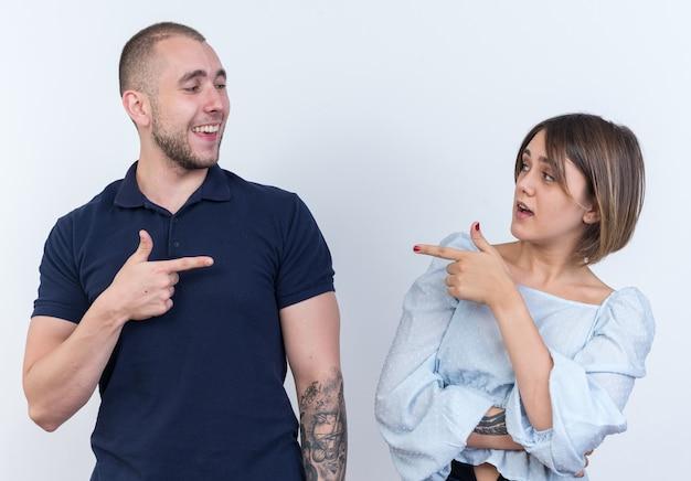 Jonge mooie paar man en vrouw kijken elkaar aan en wijzen met wijsvingers naar elkaar glimlachend gelukkig en positief staand