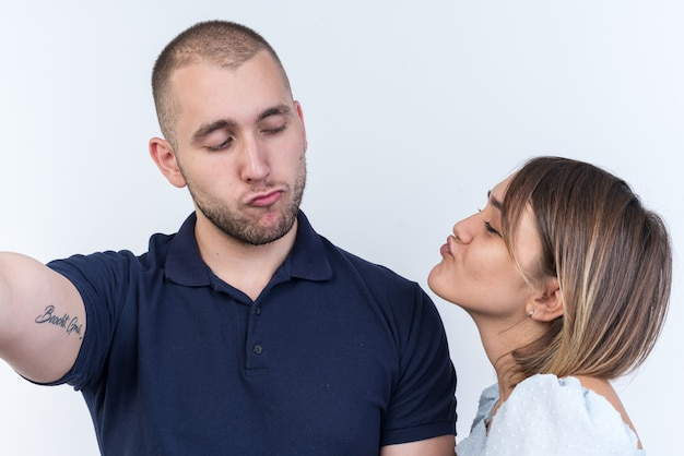 Jonge, mooie paar man en vrouw kijken elkaar gelukkig verliefd aan en gaan elkaar kussen terwijl ze over een witte muur staan