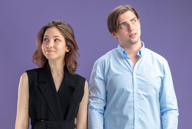 Jonge mooie paar man en vrouw kijken opzij met glimlach op gezichten gelukkig en positief vieren valentijnsdag staande over blauwe muur