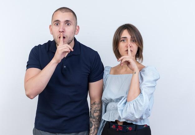 Jonge mooie paar man en vrouw kijken stilte gebaar maken met vingers op lippen permanent
