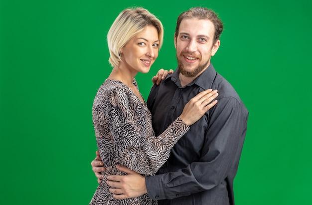 Jonge mooie paar man en vrouw lachend vrolijk gelukkig verliefd samen vieren valentijnsdag staande over groene muur