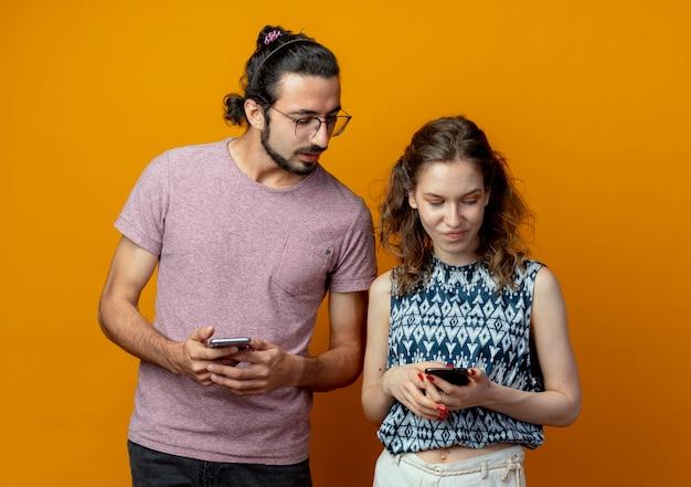 Jonge mooie paar man en vrouw, man spionage en gluren naar mobiel van zijn vriendin over oranje achtergrond