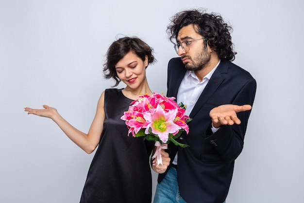 Jonge, mooie paar man en vrouw met een boeket bloemen die glimlachen en er verward uitzien met opgeheven armen om valentijn te vieren