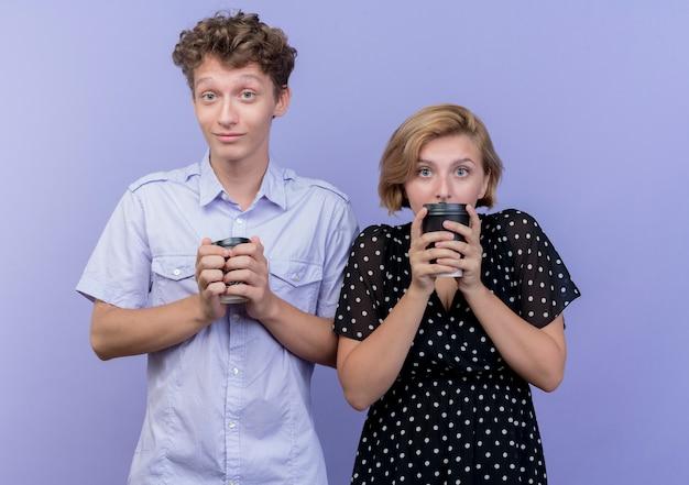 Jonge mooie paar man en vrouw met koffiekopjes verward en bezorgd staande over blauwe muur