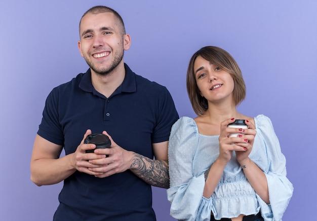 Jonge, mooie paar man en vrouw met papieren bekers die er vrolijk vrolijk en positief uitzien glimlachen
