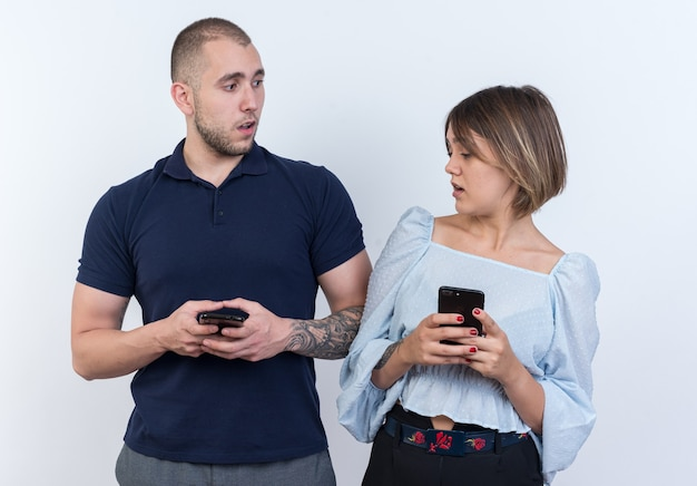 Jonge mooie paar man en vrouw met smartphones verwarde vrouw die achterdochtig kijkt naar haar vriendje smartphone staand
