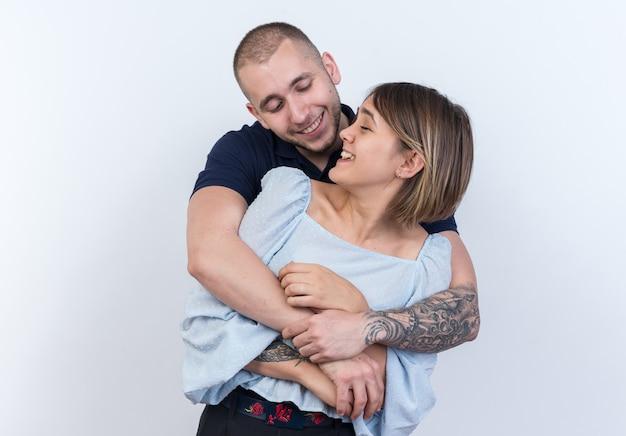 Jonge mooie paar man en vrouw omarmen glimlachend vrolijk gelukkig verliefd samen staan