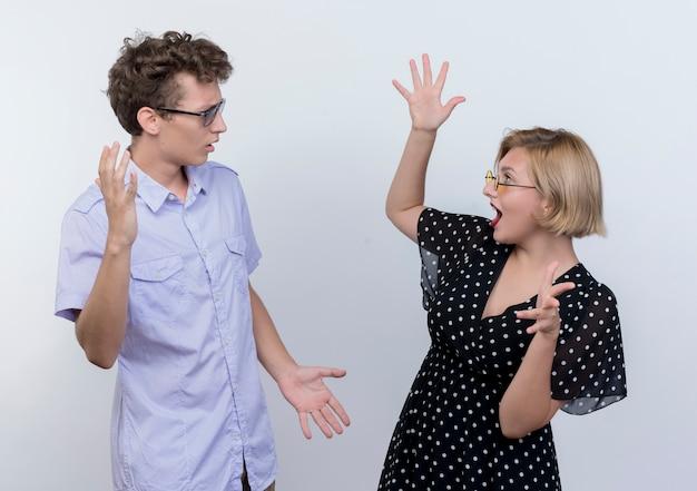 Jonge mooie paar man en vrouw ruzie gebaren met handen over wit