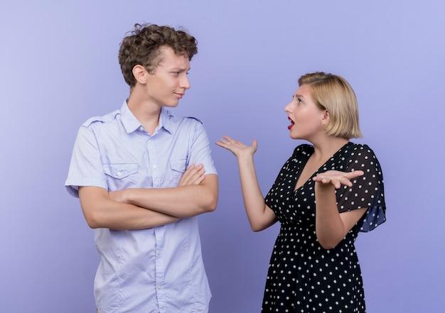 Jonge mooie paar man en vrouw ruzie vrouw op zoek verward spreidende armen naar de zijkanten over blauwe muur