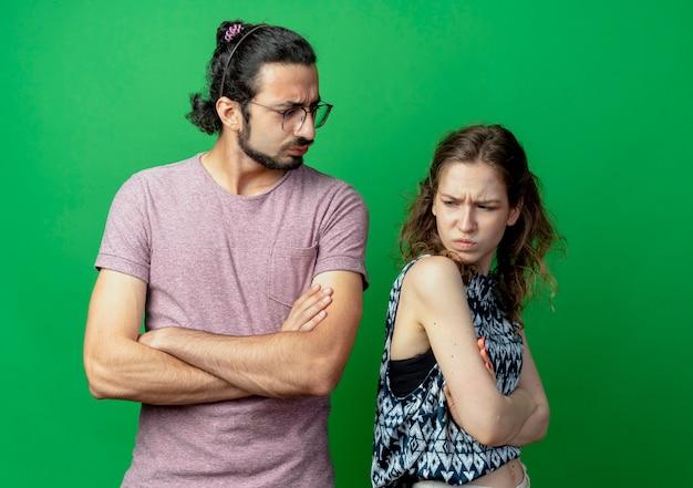 Jonge mooie paar man en vrouw staan rug aan rug fronsen en ruzie met gekruiste armen over groene muur