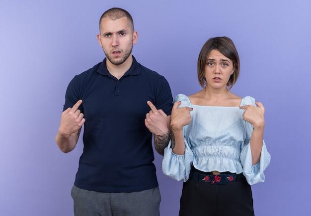 Jonge, mooie paar man en vrouw verward wijzend naar zichzelf terwijl ze over de blauwe muur staan