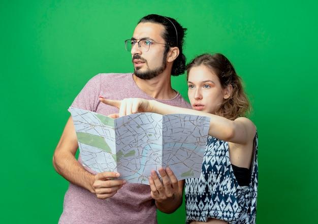 Jonge mooie paar man en vrouw, verwarde man opzij kijken terwijl zijn vriendin met vinger naar iets op groene achtergrond wijst