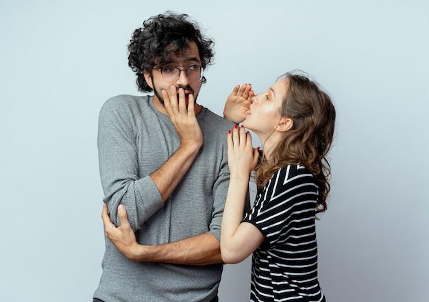 Jonge mooie paar man en vrouw, vrouw fluisteren geheime of interessante roddels aan haar vriendje op witte achtergrond