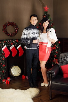 Jonge mooie paar met glazen champagne in kerstmis, donker interieur