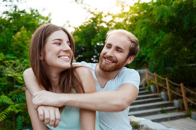 Jonge mooie paar omarmen, glimlachen, wandelen in het park outdoor muur.