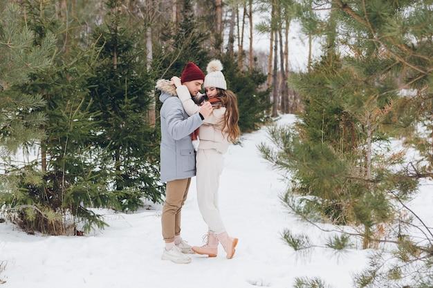 Jonge mooie paar omhelst in een winter naaldbos