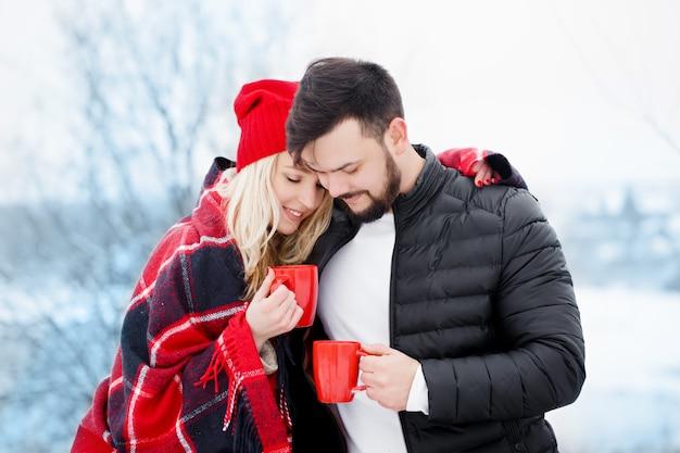 Jonge mooie paar op een picknick in de winter drinken ze koffie