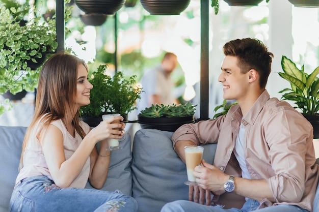 Jonge mooie paar praten en koffie drinken op het zomerterras van het café