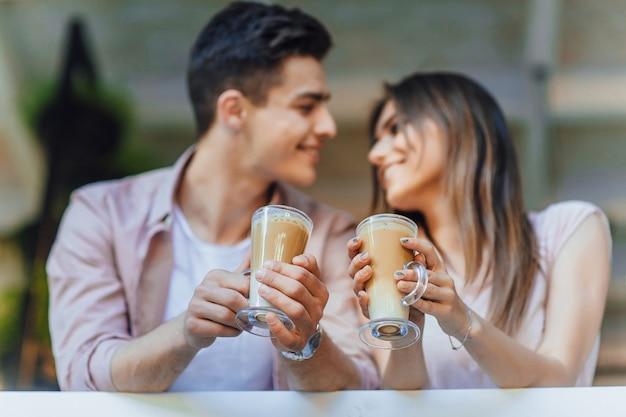 Jonge mooie paar praten op het terras in casual kleding met latte in hun handen
