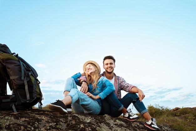 Jonge mooie paar reizigers genieten van uitzicht op canyon, glimlachend