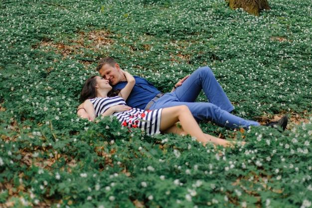 Jonge mooie paar verliefd in het bos. een man en een vrouw liegen en knuffelen in de kleuren van het lentebos. even voor de kus. detailopname. vrije ruimte.