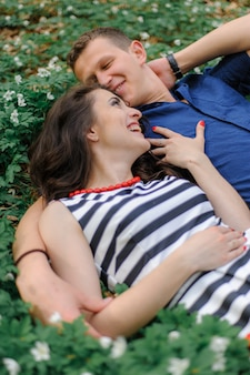 Jonge mooie paar verliefd in het bos. een man en een vrouw liggen en knuffelen in de kleuren van het lentebos op hun rug. zij zijn erg gelukkig. even voor de kus. detailopname. vrije ruimte.