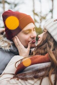 Jonge mooie paar verliefd knuffels en kusjes in een winter naaldbos. een park met kerstbomen op de achtergrond. kerststemming. verven.