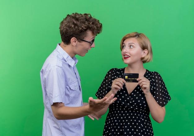 Jonge mooie paar verrast man kijken naar gelukkige vriendin die creditcard bedrijf staande over groene muur