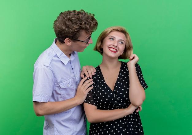 Jonge mooie paar verraste man die zijn geliefde vriendin bekijkt die in grote lijnen over groene muur glimlacht