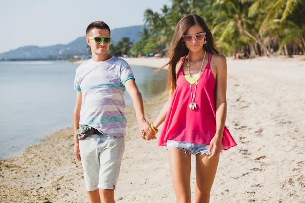 Jonge mooie paar wandelen op tropisch strand in thailand, hand in hand, glimlachen, gelukkig, plezier hebben, zonnebril, hipster outfit, casual stijl, honingmaan, vakantie, zomer, zonnig