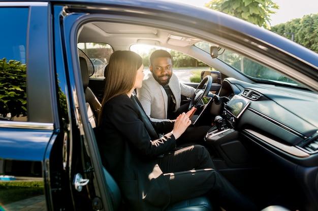 Jonge mooie paar, zakelijke partners, multiethnische man en vrouw, met behulp van tablet in de auto zakenreizen