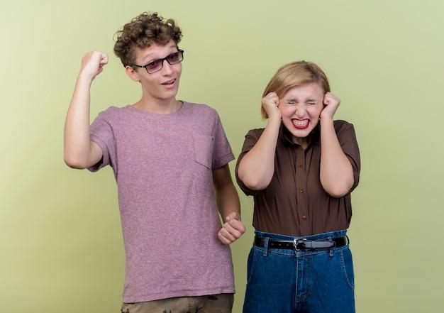 Jonge mooie paarjongen en meisje die vrijetijdskleding dragen, blij en opgewonden gebalde vuisten die zich over lichte muur bevinden