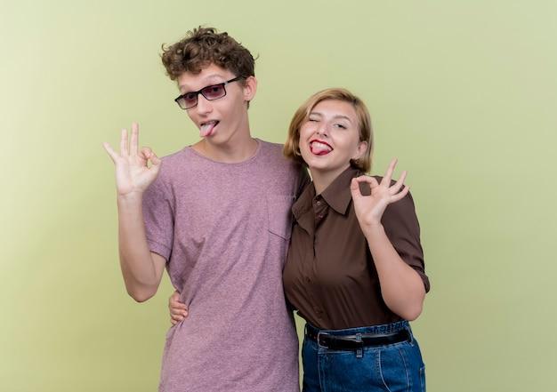 Jonge mooie paarjongen en meisje die vrijetijdskleding dragen die pret glimlachen die uit tongen uitsteekt die ok teken over licht tonen