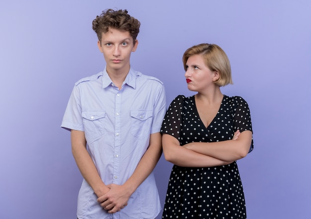 Jonge mooie paarman en vrouw die boze vrouw ruzie maken die haar ontevreden vriendje bekijken die zich over blauwe muur bevindt