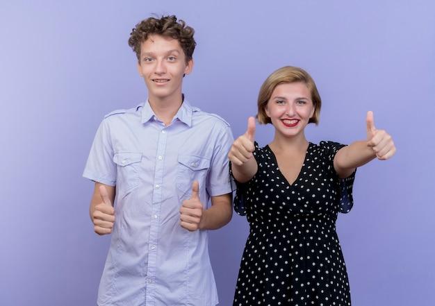 Jonge mooie paarman en vrouw die gelukkig en positief glimlachen tonen duimen die omhoog zich over blauwe muur bevinden