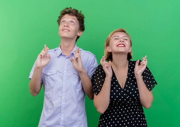 Jonge mooie paarman en vrouw die het maken van wenselijke wens kruisen die vingers met hoopuitdrukking kruisen die zich over groene muur bevinden