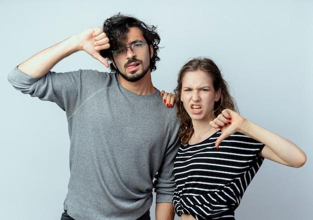 Jonge mooie paarman en vrouw die ontevreden duimen over witte muur tonen