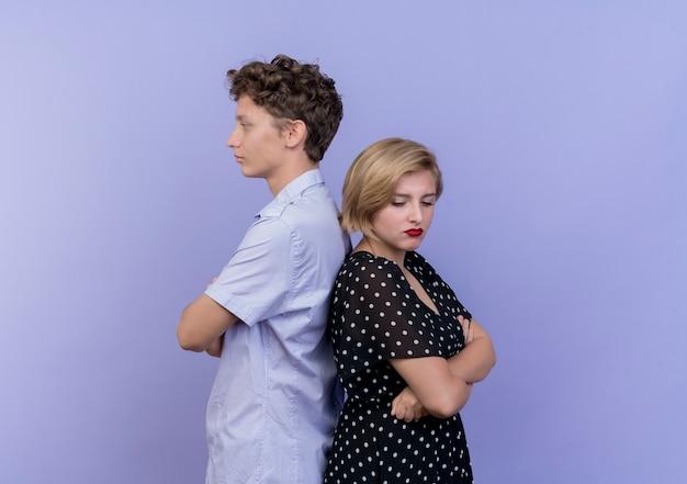 Jonge mooie paarman en vrouw die zich rijtjes bevinden die zich over blauwe muur fronsen