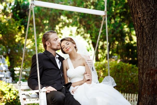 Jonge mooie pasgetrouwden glimlachen, kussen, zittend op schommel in park.