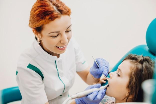 Jonge mooie pediatrische tandarts werken tijdens het vullen van een kindertanden.