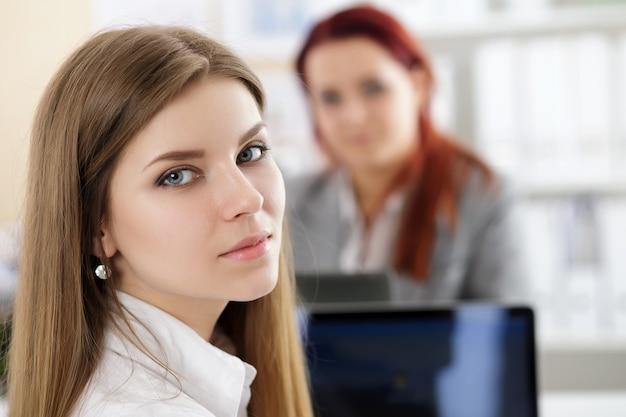 Jonge mooie peinzende zakenvrouw zittend op haar werkplek op kantoor