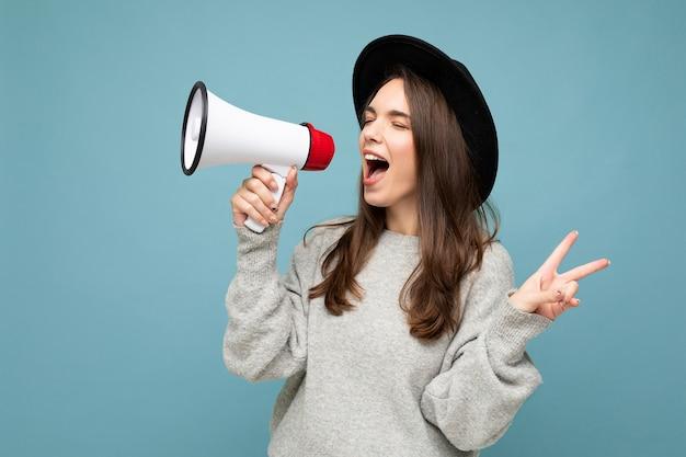 Jonge mooie positieve brunette vrouw met oprechte emoties stijlvolle zwarte hoed dragen en