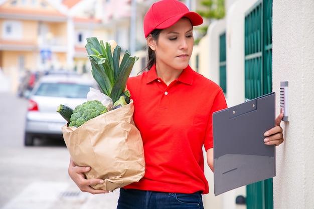 Jonge mooie postbode met papieren zak en rinkelende deurbel. zelfverzekerde brunette bezorger in rood uniform doet haar werk en levert bestelling te voet. voedselbezorgservice en postconcept