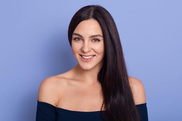 Jonge mooie prachtige jonge vrouw met perfecte huid donker blauwe jurk poseren met blote schouders dragen
