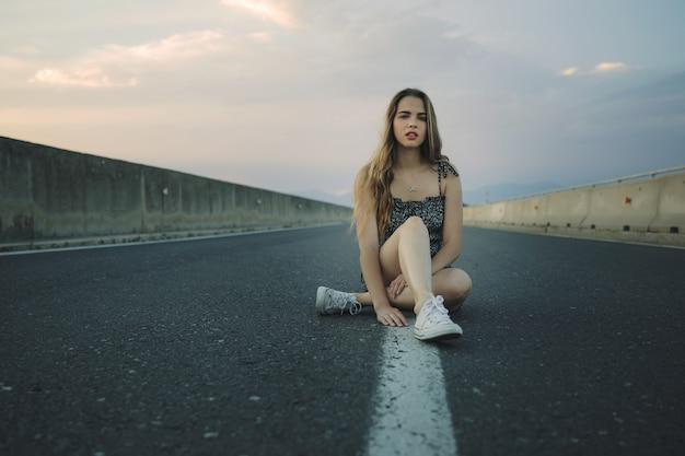 Jonge mooie rebellenvrouw op lege weg bij zonsondergang