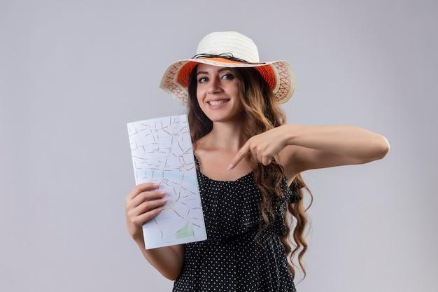 Jonge mooie reiziger meisje in jurk in polka dot in zomer hoed bedrijf kaart wijst met vinger naar het glimlachend vrolijk staande op witte achtergrond