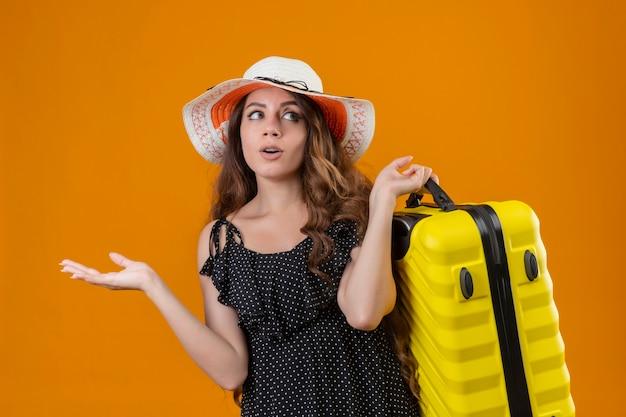 Jonge mooie reiziger meisje in jurk in polka dot in zomer hoed bedrijf koffer op zoek clueless en verward twijfels staande over gele achtergrond